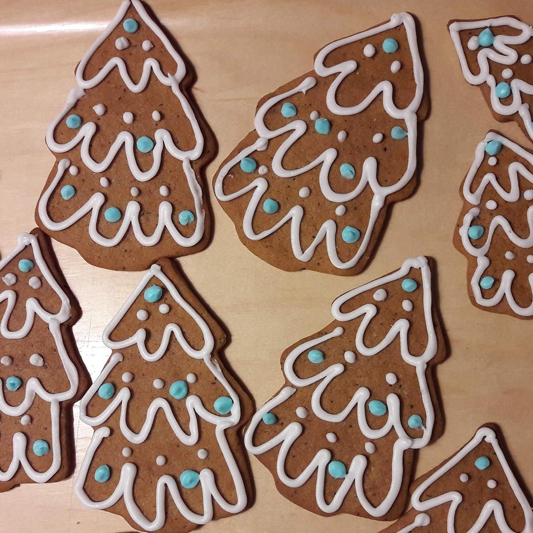 Kuusenmuotoiset joulupiparkakut koristeltuina tomusokerikuorrutuksella.