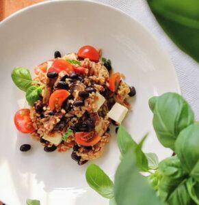 kaura-papupata valkoisella lautasella, vieressä basilikanoksa