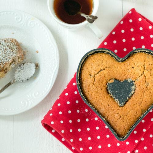 Hedelmäkakku sydänvuoassa, pöydällä kahvikuppi ja kakkulautanen