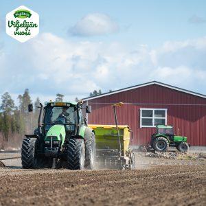 Traktorit työssä pellolla taustalla punainen talli