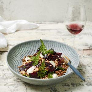 ruoka-annos lautasella, vieressä lasi viiniä